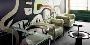 Reproduction d'une fresque peinte par Le Corbusier derrière des meubles dessinés par ce dernier et Charlotte Perriand.