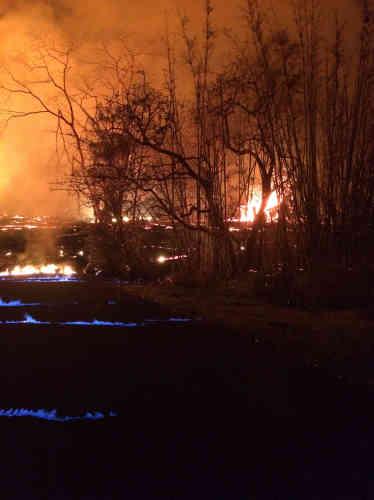Les flammes bleues au premier plan sont dues à la combustion du méthane qui s'échappe des fissures sur une chaussée, à Pahoa, le 23 mai. Un volcan produit du méthane lorsque des végétaux sont ensevelis sous de la lave incandescente.