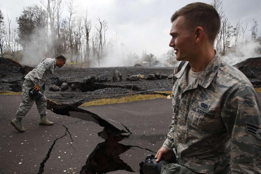 Des militaires observent des fissures sur une route dans un lotissement résidentiel, signe que le magma du volcan Kilauea cherche un passage vers la surface, près de Pahoa, le 18mai.