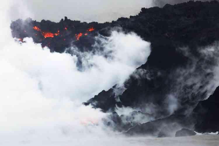 Les flots de lave qui s'échappent des fissures apparues sur le flanc du volcan Kilauea se déversent dans l'océan Pacifique, près de Pahoa, le 22mai. La vapeurqui s'en dégage contient notamment de l'acide chlorhydrique.