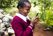 Isabellah, 9ans, teste l'application M-Shule dans la cour de son école, dans le comté de Muranga, au Kenya.