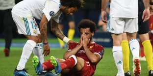 Liverpool's Egyptian forward Mohamed Salah (C) reacts after an injury as Real Madrid's Brazilian defender Marcelo (L) leans down to him during the UEFA Champions League final football match between Liverpool and Real Madrid at the Olympic Stadium in Kiev, Ukraine, on May 26, 2018. / AFP / FRANCK FIFE