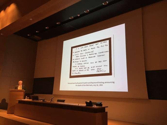 James Watson, le 23 mai au Collège de France, présentant un «avis de décès de l'ADN en spirale» humoristique rédigé par Rosalind Franklin, le 18 juillet 1952.