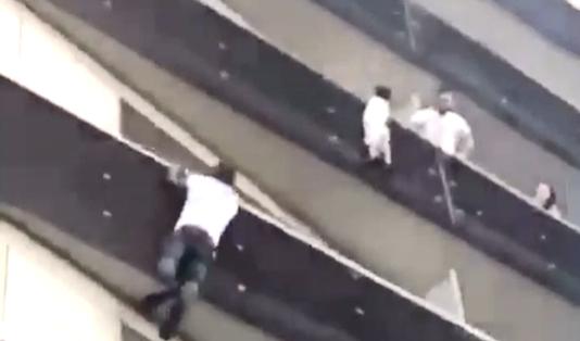 Mamoudou Gassama escaladant quatre étages pour récupérer l'enfant suspendu par une main dans le vide, à Paris, le 26 mai.