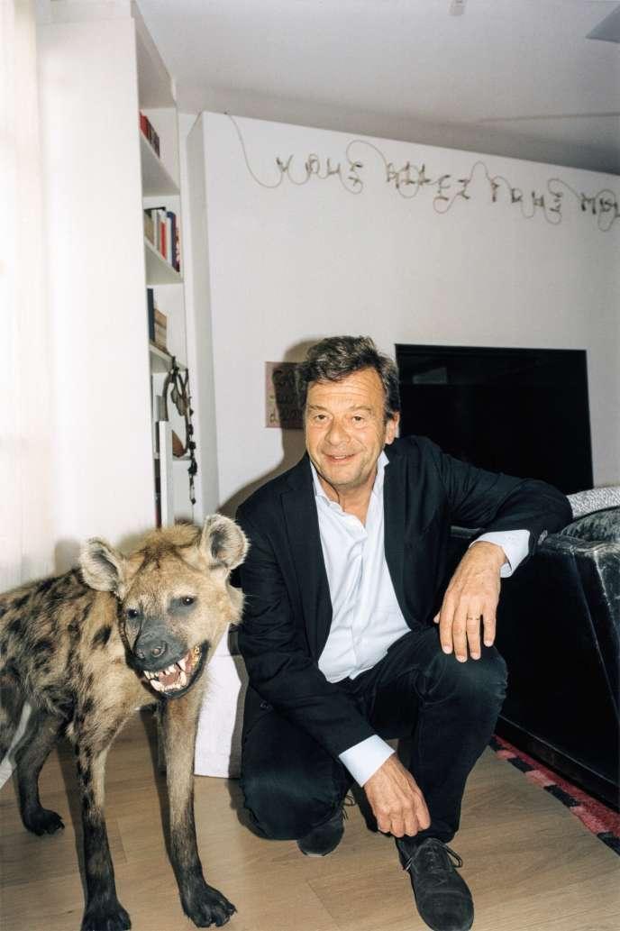 Antoine de Galbert, le 28 avril 2018, dans sa réserve à Paris, au côté d'une hyène naturalisée avec des molaires en or,œuvre de Nicolas Milhé.