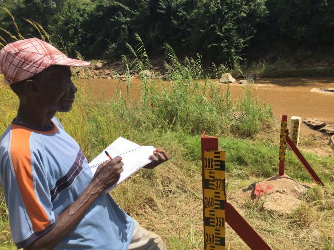 Un paysan relève le niveau de l'eau, indiqué par une jauge solidement plantée au milieu des flots terreux de la rivière Lifisi, au Malawi.