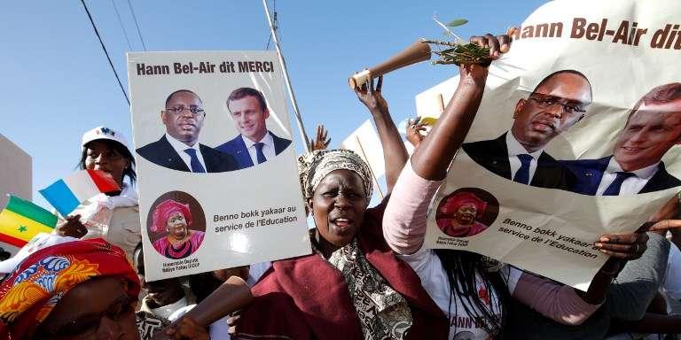 Des partisans du président sénégalais agitent des pancartes sur lesquelles figurent Macky Sall et Emmanuel Macron lors de l'inauguration d'un collège à Dakar, le 2 février 2018.
