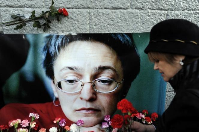 Une femme pose une fleur à côté de la photo de la journaliste AnnaPolitkovskaïa, assassinée en 2009 à Moscou.