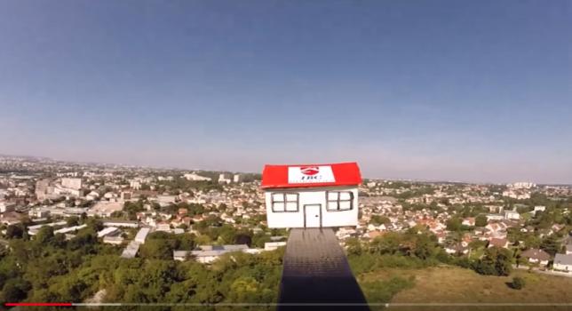 Une petite maison siglée du logo d'une agence immobilière décolle au-dessus de la ville de Gagny, en Seine-Saint-Denis.