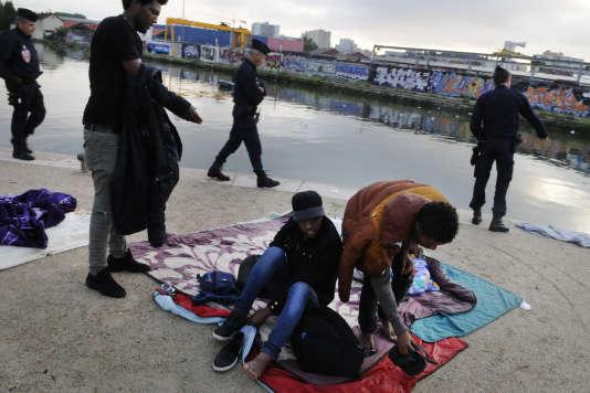 Trois réfugiés d'origine Erythréenne se préparent à être évacués, le long du canal Saint-Denis, le 30 mai.