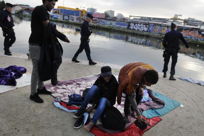 Trois migrants érythréens se préparent à être évacués, le long du canal Saint-Denis, le30mai.