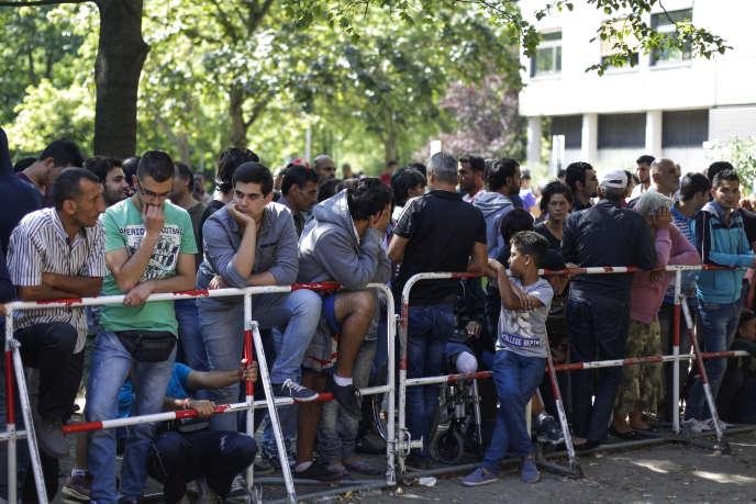 Des personnes patientent devant un centre d'accueil pour les réfugiés et demandeurs d'asile à Berlin, le 21 août 2015.