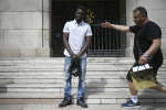A passer by arrives to take a selfie with a 22-year old Mamoudou Gassama from Mali in front of the townhall of Montreuil, eastern Paris suburb, on May 28, 2018. Mamoudou Gassama living illegally in France is being honored by French President for scaling an apartment building on May 26 to save a 4-year-old child dangling from a fourth-floor balcony. / AFP PHOTO / Lionel BONAVENTURE