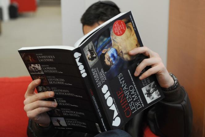 Un homme lit la revue «6Mois», le 22 mars 2011 à Paris.
