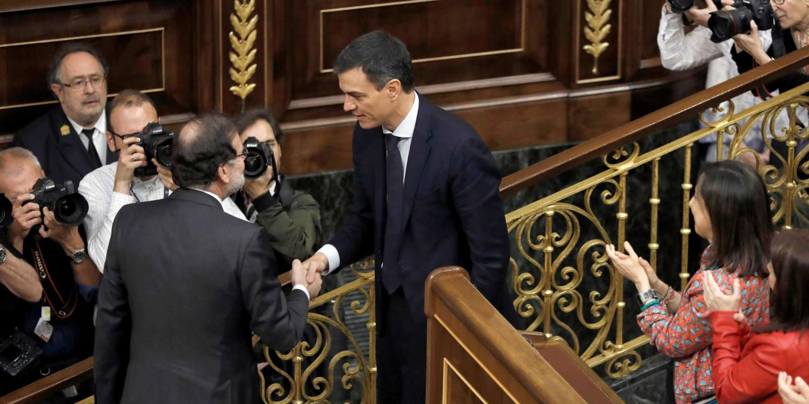 Spanish out-going Prime Minister Mariano Rajoy (L) shakes hands with Spain's new Prime Minister Pedro Sanchez after a vote on a no-confidence motion at the Lower House of the Spanish Parliament in Madrid on June 01, 2018. Spain's parliament ousted on June 1, 2018 Prime Minister Mariano Rajoy in a no-confidence vote sparked by fury over his party's corruption woes, with his Socialist arch-rival Pedro Sanchez automatically taking over. / AFP / POOL / Emilio Naranjo