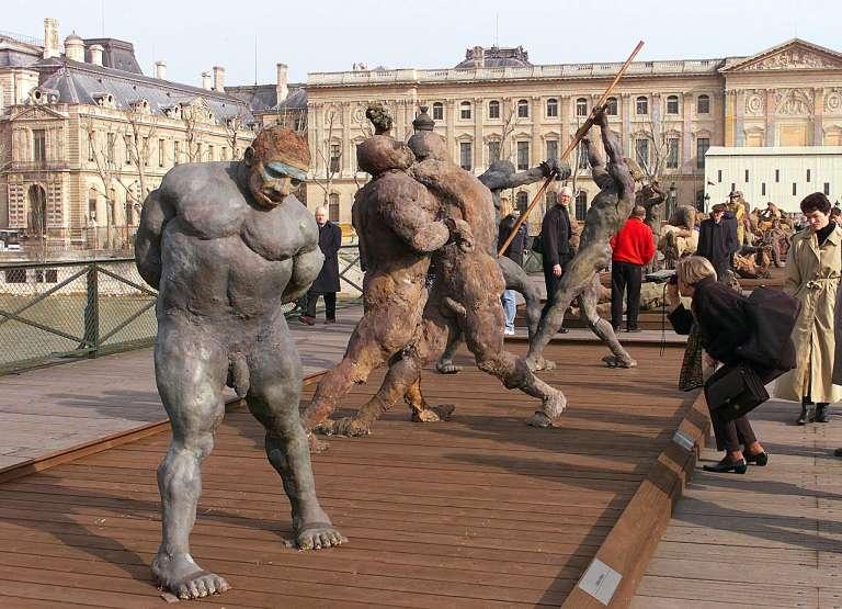 Des touristes et des Parisiens regardent, le 19 mars 1999 sur le pont des Arts à Paris, les sculptures du Sénégalais Ousmane Sow.