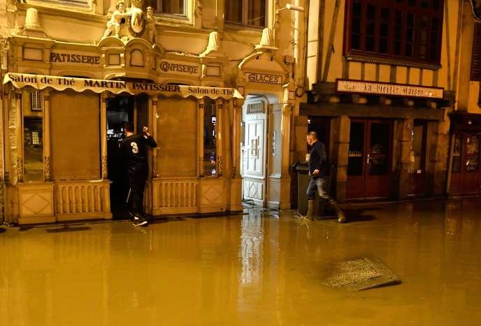 Les propriétaires d'une boulangerie tentent d'évacuer l'eau et la boue de leur local, dimanche soir àMorlaix.