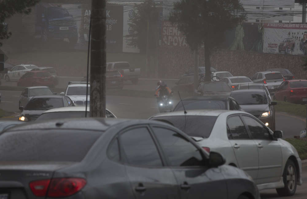 Des automobilistes se frayent un chemin à travers une légère pluie de cendres volcaniques, à Guatemala City.L'éruption a touché notamment la cité coloniale d'Antigua, le plus important site touristique du Guatemala.