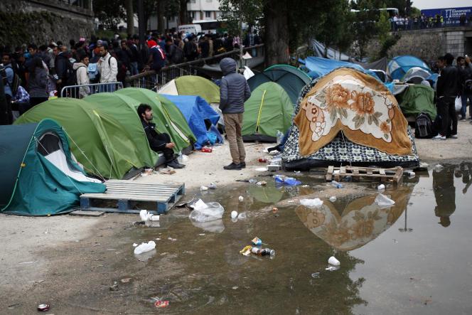 Des migrants attendent de partir lors d'un déblaiement d'un camp de fortune le long du canal Saint Martin, dans le centre de Paris, le lundi 4 juin 2018. La police française a évacué environ 500 migrants, principalement des Afghans, mais aussi des Africains, d'un campement de tentes de fortune.