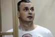 FILE - In this Aug. 25, 2015 file photo, Oleg Sentsov stands behind bars as his verdict is read at a court in Rostov-on-Don, Russia. Sentsov, a prominent Ukrainian filmmaker, was convicted of conspiring to commit terror attacks and sentenced him to 20 years in prison.  Margaret Atwood, Stephen Sondheim and Patrick Stewart are among dozens of artists and journalists calling for the release of Sentsov,  a critic of Russia's annexation of Crimea. (AP Photo, File)