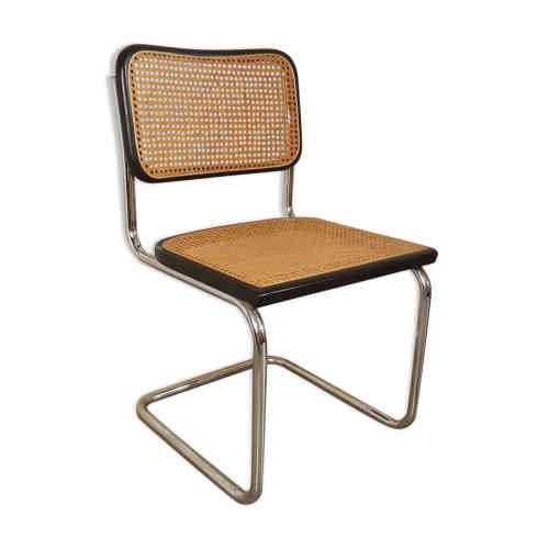 La Chaise Breuer B32 CESCA : cette chaise, comme une calligraphie dans l'espace, est signée de l'architecte et designer d'origine hongroise Marcel Breuer (1902-1981), l'un des maîtres du Bauhaus. Il dessine cette forme en 1928, avec une base en acier tubulaire, une assise et un dossier en canne de Vienne. Façon pionnier du modernisme.