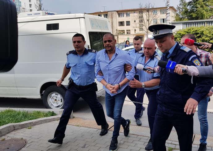 L'Italien Nicola Inquieto escorté par des policiers roumains, le 12 avril, lors de l'opération « Transylvania ». Denis Grigorescu