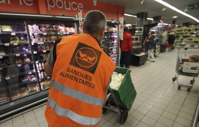 Un bénévole des banques alimentaires récolte des dons dans un supermarché de L'Haÿ-les-Roses (Val-de-Marne), en mai 2015.