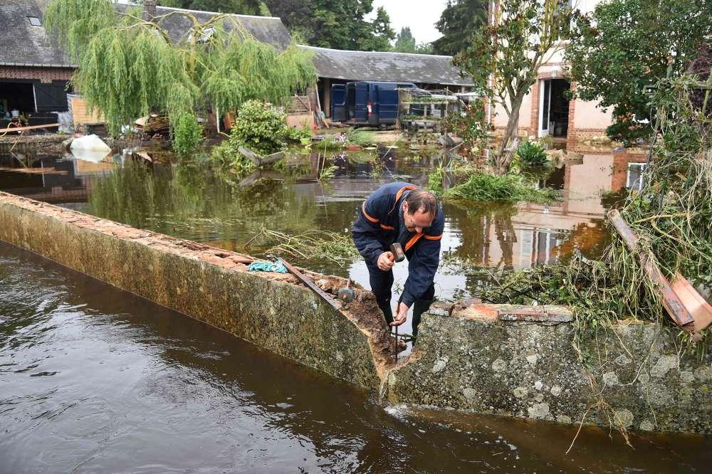 Un résident creuse le mur de sa propriété pour évacuer l'eau stagnante de sa cour à La Guéroulde (Eure). La crue de l'Iton continue d'inonder l'Eure, où plus de 600foyers ont été privés d'électricité. Les sapeurs-pompiers ont mené plus de 300interventions, et évacué une douzaine de personnes.