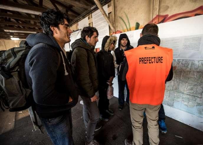 Un employé de la préfecture parle avec des migrants afghans, près de la« jungle» de Calais, le 14 janvier 2016.