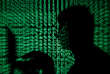 FILE PHOTO: A man holds a laptop computer as cyber code is projected on him in this illustration picture taken on May 13, 2017. REUTERS/Kacper Pempel/File Photo