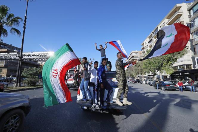 Des Syriens prorégime brandissent les drapeaux syrien, iranien et russe, à Damas, le 14 avril.