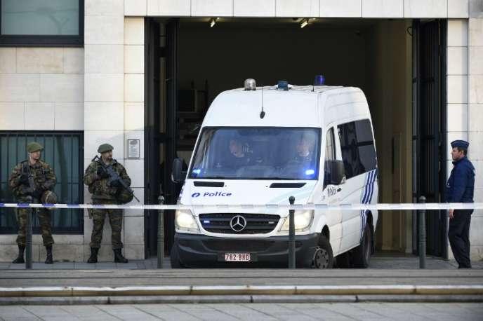 Un véhicule de police quitte le tribunal de Bruxelles le 14avril 2016 après l'audition de plusieurssuspects clé des attentats de Paris et Bruxelles, dontOsama Krayem