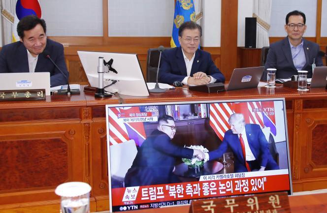 Moon Jae-in (au centre), le président sud-coréen, et Lee Nak-yon, son premier ministre, regardent les images de la poignée de main historique de Trump et Kim, le 12 juin à Séoul.