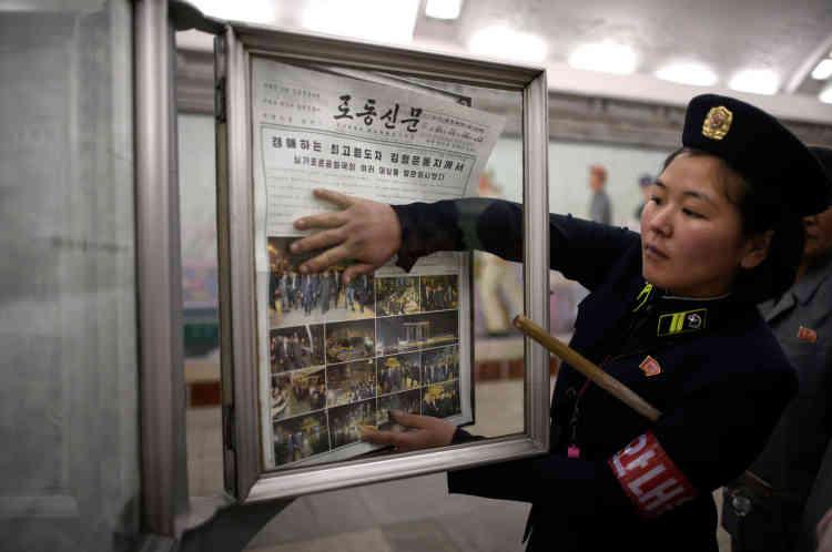 Le 12 juin, dans une station du métro de Pyongyang, une chef de train affiche l'édition d'un quotidien montrant des photos du leader nord-coréen à Singapour.