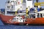 Un bateau des garde-côtes italiens accoste l'Aquarius pour transférer des migrants, mer Méditerranée, 12 juin 2018.