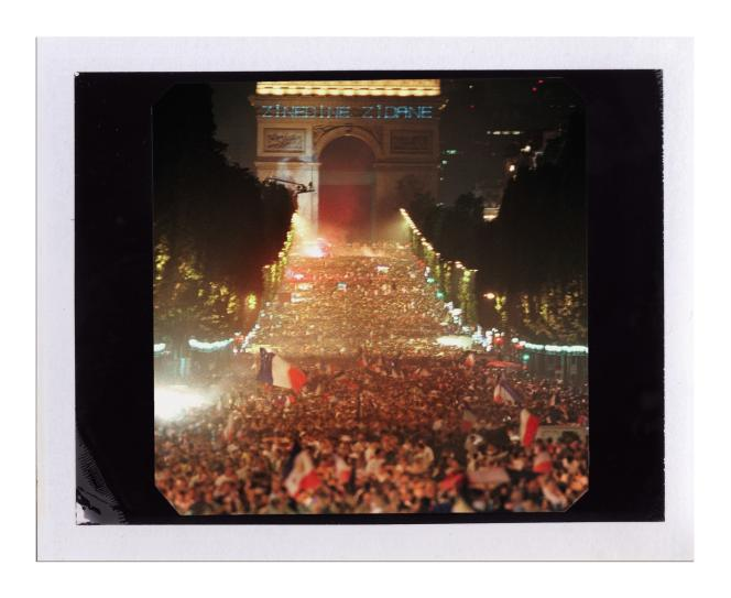 Les Champs-Élysées assaillis par la foule de fêtards, le 12juillet 1998. Le portrait de Zidane est projeté sur l'Arc de triomphe.