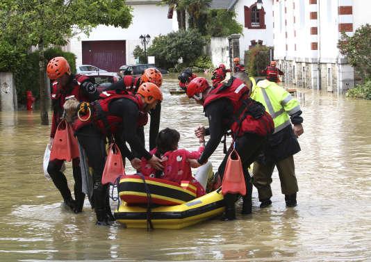 Des pompiers évacuent une personne âgée à Salies-de-Béarn, mercredi 13 juin.
