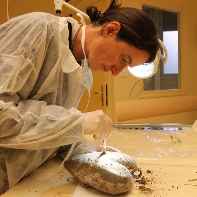 Rozenn Colleter nettoie une urne en plomb à l'unité de médecine légale du CHU Rangueil de Toulouse, en mai 2014.