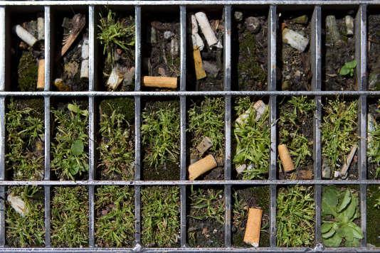 Des mégots de cigarettes jonchant le sol.