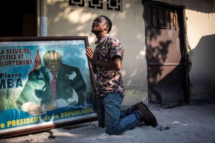 Un soutien de Jean-Pierre Bemba prie à côté du portrait de l'ex-vice-président de la République démocratique du Congo, le 8 juin à Kinshasa.