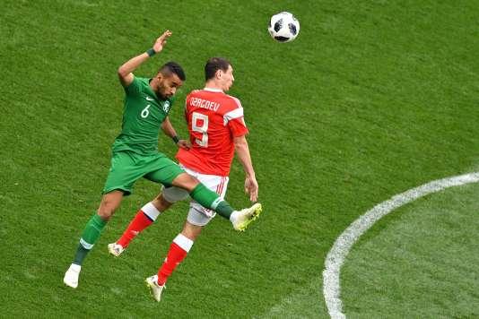 Le défenseur saoudien Mohammed Al-Breik au duel avec le milieu de terrain Alan Dzagoev, jeudi 14 juin, en match d'ouverture du Mondial 2018.