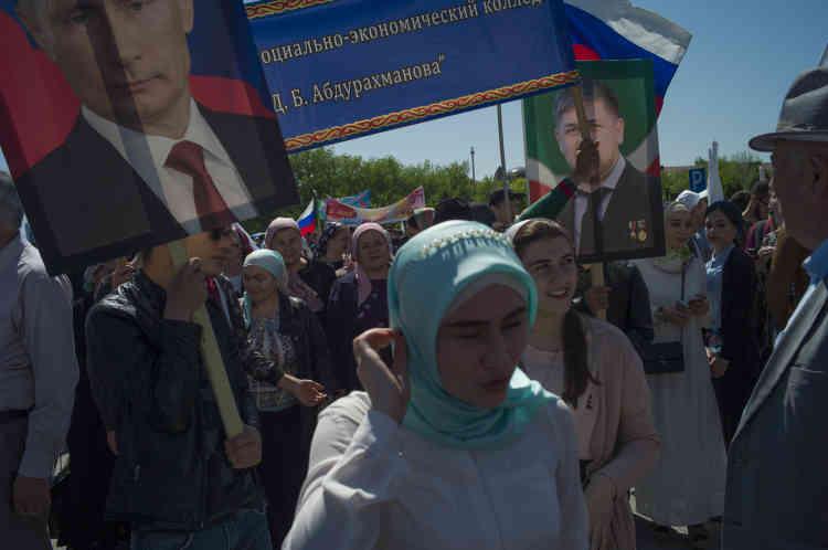 Des étudiants et des fonctionnaires brandissent des portraits de Vladimir Poutine et de Ramzan Kadyrov lors du rassemblement du 1er-Mai.