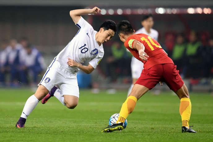 Le Sud-Coréen Nam Tae-hee etle Chinois Zheng Zhi lors des éliminatoires de la zone Asie pour la Coupe du monde 2018, à Tchang-cha, province de Hunan( Chine), le 23 mars 2017.