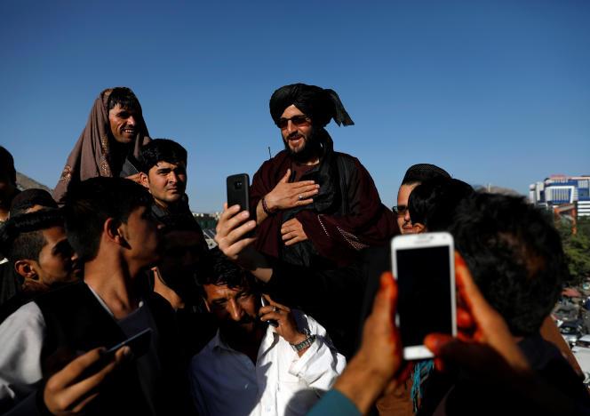 Des habitants prennent des selfies avec un taliban à Kaboul, le 16 juin.