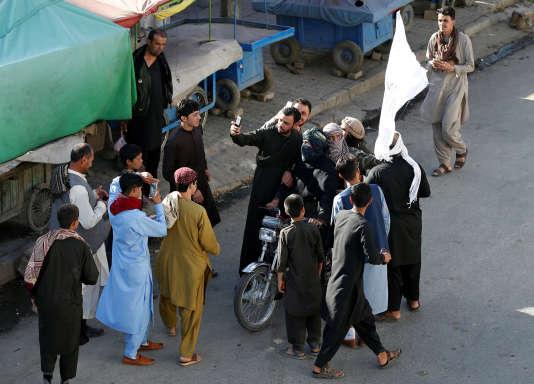 Des Afghans se prennent en photo avec des talibans pour célébrer le cessez-le-feu, le 16 juin à Kaboul.