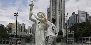 Un homme nettoie le visage de la statue de la déesse de la Démocratie dans le parc Victoria, à Hong Kong, le 4 juin.
