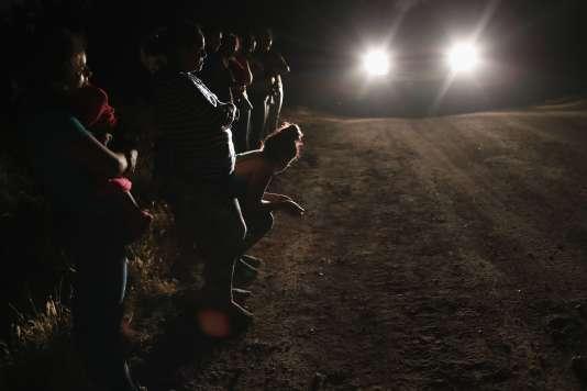 Des demandeurs d'asile, dont une petite fille hondurienne de 2 ans et sa mère (àgauche), attendent leur incarcération, près de McAllen, au Texas.