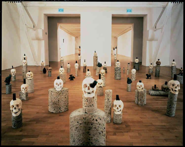 «Œuvre emblématique des années sculptures au titre aussi énigmatique que l'œuvre elle-même. Intérêt pour la mort avec laquelle Erik Dietman flirtera jusqu'au baiser final. Réflexion sur la création, repartir du carré que les têtes fixent sur le mur qui leur fait face.»