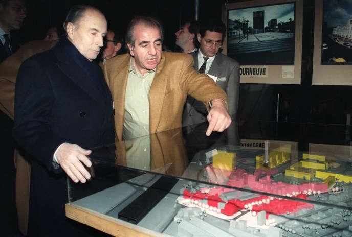 François Mitterrand écoute les explications de l'architecte Roland Castro devant la maquette d'une cité de banlieue, le 4 décembre 1990.