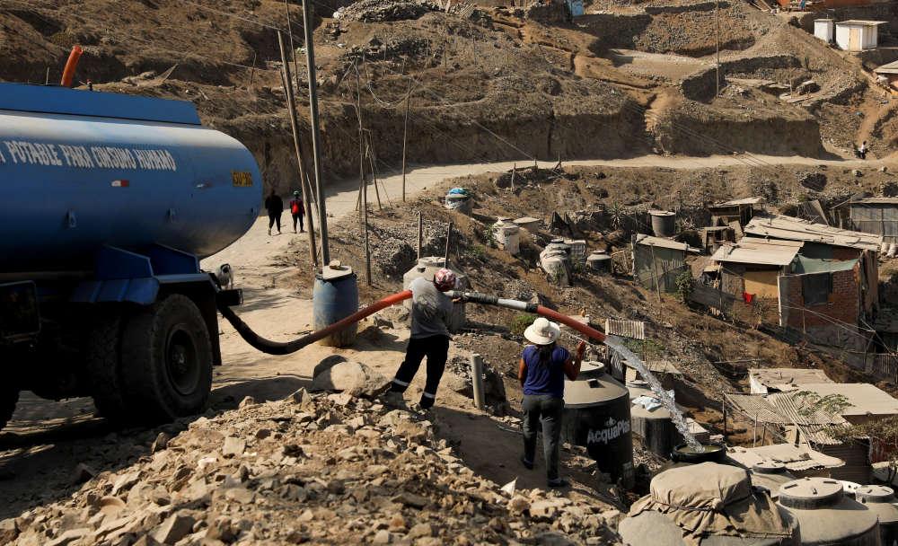 Un habitant de Nueva Union achète de l'eau d'un camion-citerne, le 7 mai. En l'absence d'accès aux services publics, l'eau n'est disposnible qu'auprès de vendeurs privés. En hiver, quand les rues deviennent glissantes, les livraisons sont souvent suspendues.